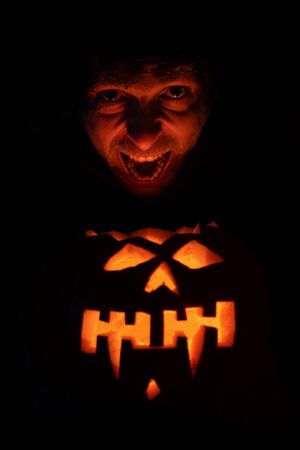 Scary face lit by Halloween pumpkin. Evil Laughing. Human Face