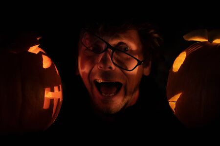 Scared man in glasses between two halloween pumpkins. Horror image of spooky flames in pumpins.