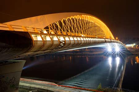 Bright modern bridge across a river in the night. Modern city architecture. Construction for traffic 版權商用圖片