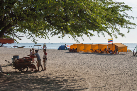 sandal tree: Santa Marta, Colombia - 07 February, 2011 -people working and relaxing in tents in Rodadero beach.