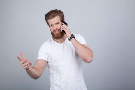 Serious handsome bearded man talking on cell phone over white background
