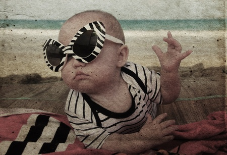 head in the sand: fashion baby on seaside. Photo in old color image style Stock Photo