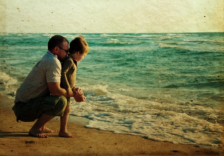 child with his father at sea. Photo in old color image style. photo