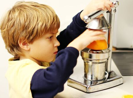 citrus family: boy squeezes juice from oranges