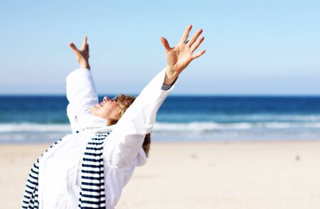 Senior Woman With Arms Outstretched On Winter Beach. Focus on the arm.  photo