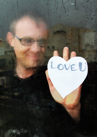 photo of young adult man standing at the window on a rainy day with paper heart Stock Photo - 12112189