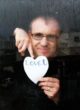 photo of young adult man standing at the window on a rainy day with paper heart photo