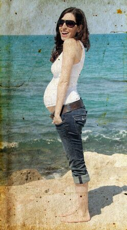 pregnant woman on the beach. Photo in old image style. photo
