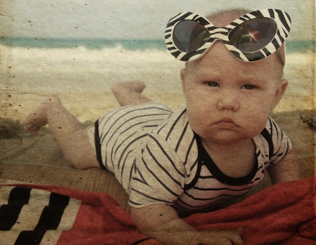 fashion baby on seaside. Photo in old color image style. photo