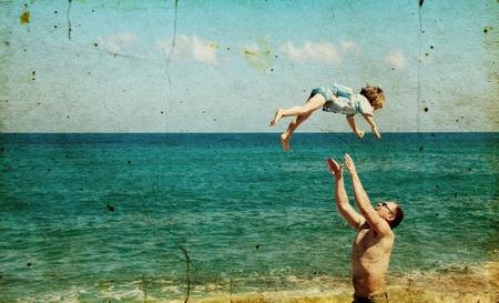 padre e hijo: Padre e hijo mirando una vela blanca en el mar. Foto en el estilo de la antigua imagen.