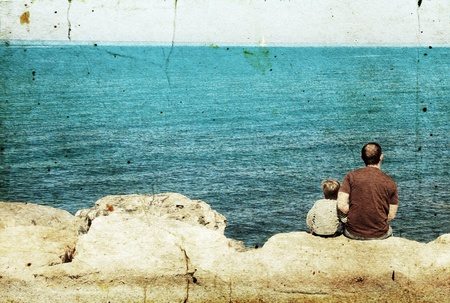 Father and son looking at a white sail in the sea Stock Photo