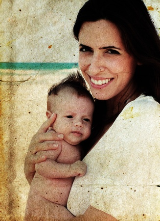 beautiful mother with her baby on the beach. Photo in old color image style. photo