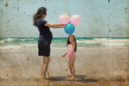 Pregnant mother with daughter on the beach with balloons photo