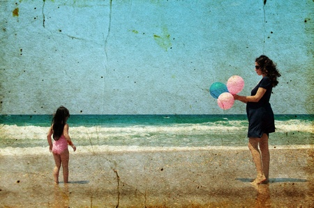 the old days: Pregnant mother with daughter on the beach with balloons