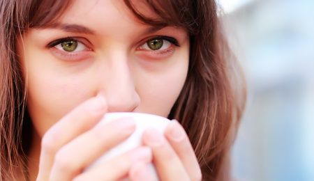 young girl with a cup of coffee. Focus on the eyes. photo