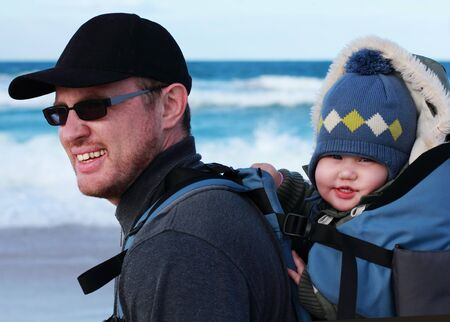 Dad with a small child walking on a winter beach. photo