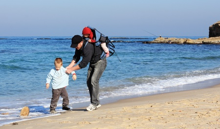 Dad, son and daughter during a walk along the sea running from the waves Stock Photo - 12119361