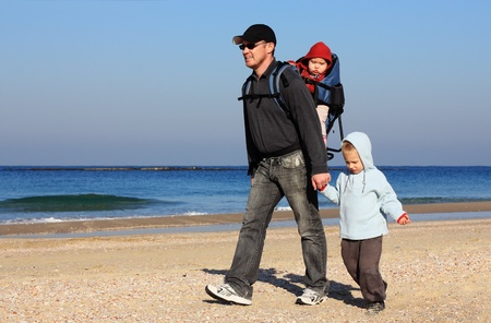 children day: Dad, son and daughter during a walk along the sea running from the waves Stock Photo