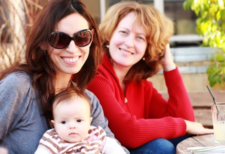 gay lifestyles: two beautiful girls with a baby outdoor