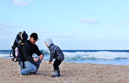 Dad and son collect shells photo