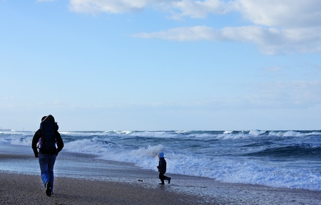 Dad with a small child walking on a winter beach. Stock Photo - 12441355