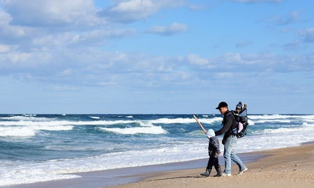 Dad with a small child walking on a winter beach. Stock Photo - 12119354