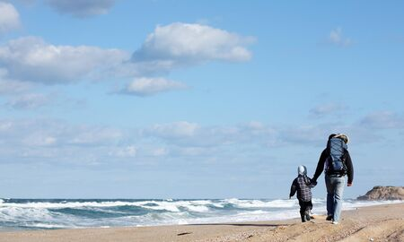 Dad with a small child walking on a winter beach. Stock Photo - 12112298