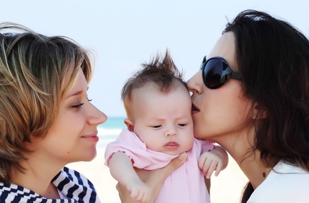 gay lifestyles: two beautiful girls with a baby on the beach