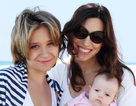 gay girl: two beautiful girls with a baby on the beach