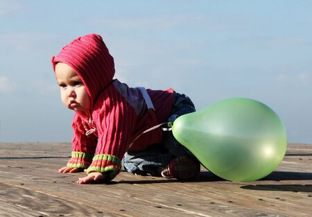 cute 10-month old baby with green baloon photo