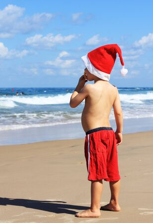 4-year-old boy in Santa Claus hat on the beach photo