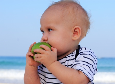 child holding a green apple in the background sea photo