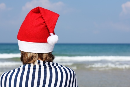 Christmas at sea. Girl in Santa hat on the beach. photo