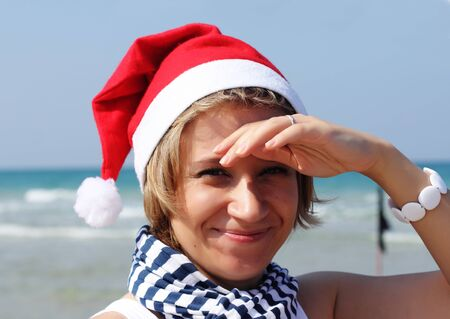 Christmas at sea. Girl in Santa hat on the beach. photo