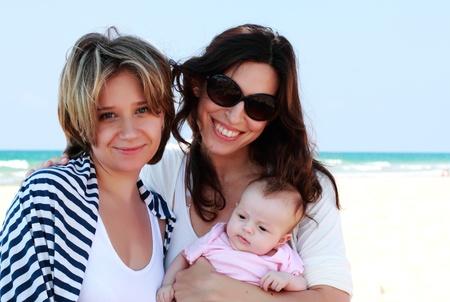 lesbianas: dos hermosas chicas con un bebé en la playa
