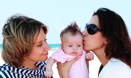 homosexuals: two beautiful girls with a baby on the beach