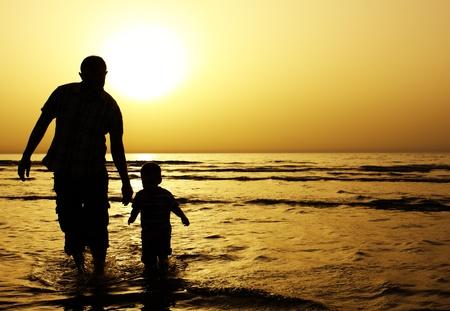 apoyo familiar: ni�o con su padre en el mar. Puesta del sol Foto de archivo