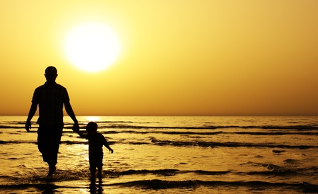 father and son: child with his father at sea. Sunset