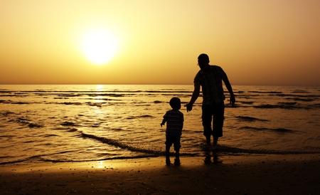 바다에서 그의 아버지와 아이. 일몰