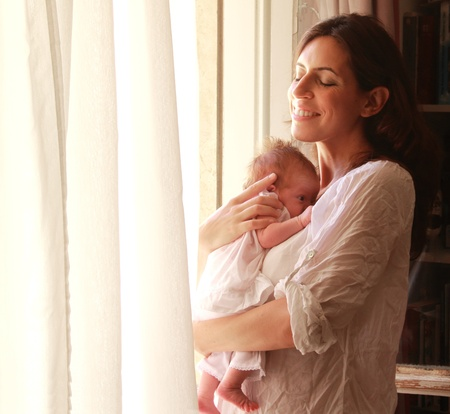 30-year-old beautiful mom is holding her newborn daughter Stock Photo