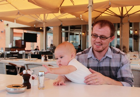 Dad with his baby daughter in a cafe ordering breakfast photo
