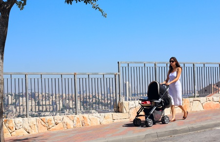 young mother walking with a stroller on the background of a big city (Jerusalem) photo