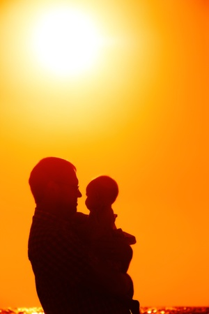 child with his father at sea on sunset photo