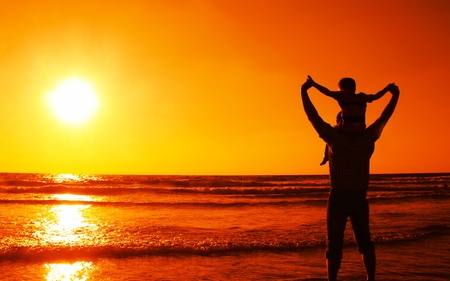 father and son holding hands: father and son at sea watching sunset