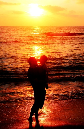 father and son at sea watching sunset photo