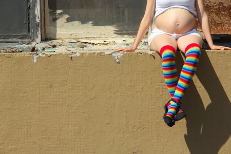 pregnant women in colorful socks sitting on the fence