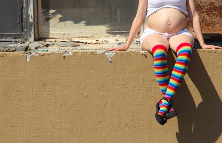 pregnant women in colorful socks sitting on the fence photo