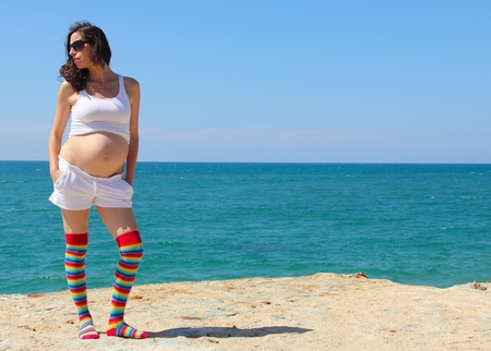 pregnant young woman against the blue sea photo