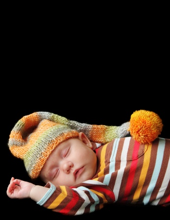 baby sleeps in a hat on a blanket photo