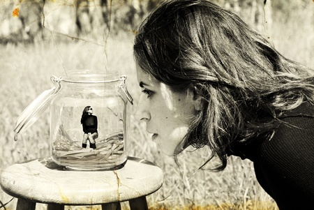 girl looks at herself in the glass jar  Photo in old image style   photo